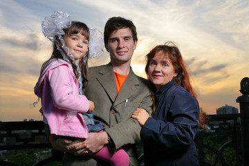 Fotobehang - Portrait of young happy family with child outdoors at sunset