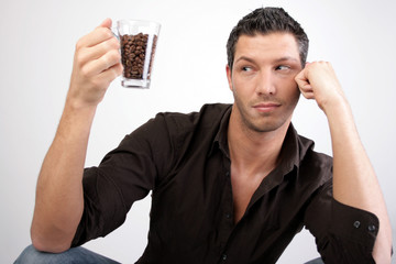 nachdenklicher mann mit kaffee und kaffeebohnen