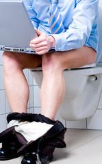 Geschäftsmann mit Notebook auf Toilette