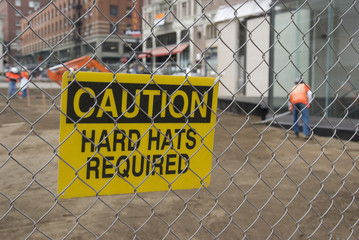 Caution, Hard Hats Required sign at a construction site.