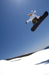snowboarder in air after jump with sunshine behind