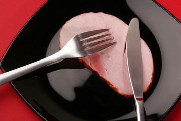 A piece of ham with place setting.