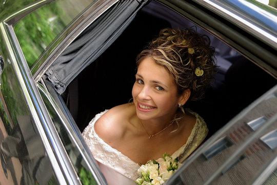 Bride in white wedding dress in wedding limo