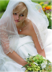 Bride in white dress with veil and bouqiet