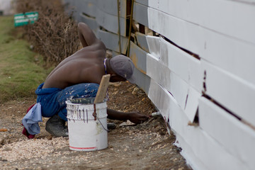 A man is painting a fence with white color