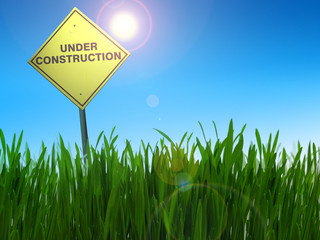 Under construction sign with sun in the blue sky and green field