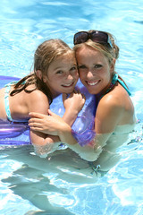 woman and little girl  in a swimming pool
