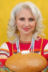 Russian woman in a folk russian dress Holds a bread