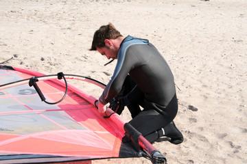 junger Mann macht sich zum Windsurfen fertig.