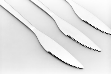 Three knives on a grey background