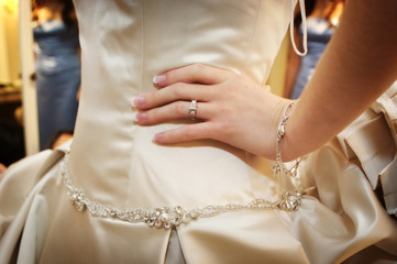 brides hand and diamond ring on hip waiting to walk down the isl