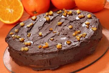 Round chocolate cake with cut fresh orange pieces