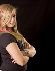 Young proud teenage girl posing on black background