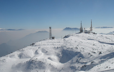 Telecommunications tower with satellite dish in winter