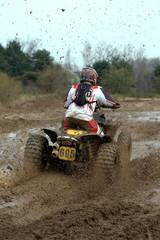 big yellow quad going through a deep mud