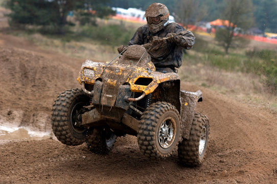 Yellow quad riding in the mud