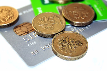Pound Coins and Credit Cards Isolated Over White