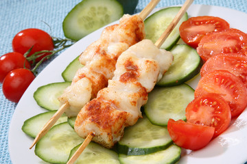Fish skewers on fresh cucumber slices and cherry tomatoes