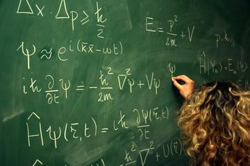 étudiante ecrivant des équations au tableau