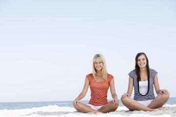 Two women sitting on beach