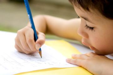 boy enjoying his his writing as part of homework,