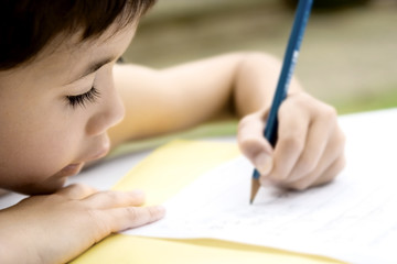 Young boy engrossed in his writing as part of homework,