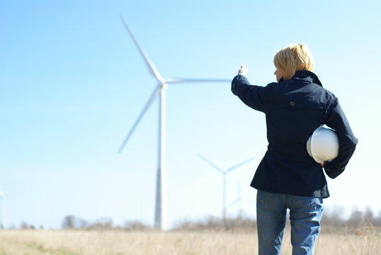 Woman engineer with white safety hat and wind turbines