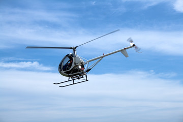 Small passenger helicopter hovering on blue sky