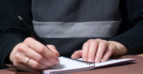 Close-up of a woman's hand with a pen writing something.