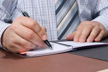 Close-up of a businessman's hand with a pen writing something.