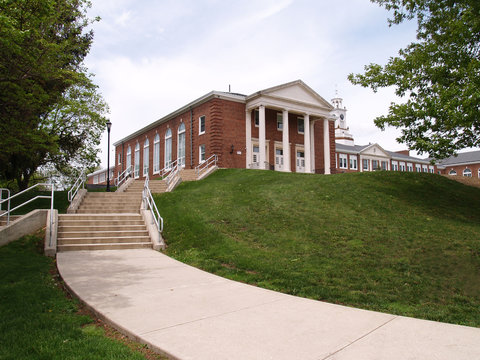 sidwalk and steps leading to an old school on a hill