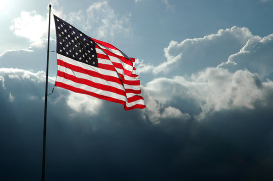 American Flag Backlit with Approaching Storm Front