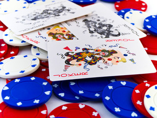 Red White and Blue Poker Chips and Jokers on White Background