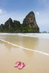 pink flip flops on deserted beach, thailand