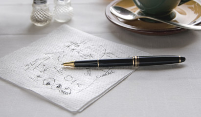 Napkin with Scribbled Notes and Pen on Table