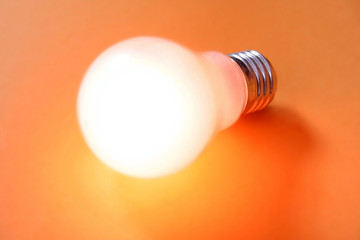Glowing light bulb turned on over a orange background