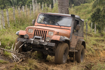 A red jeep splattered and caked with mud