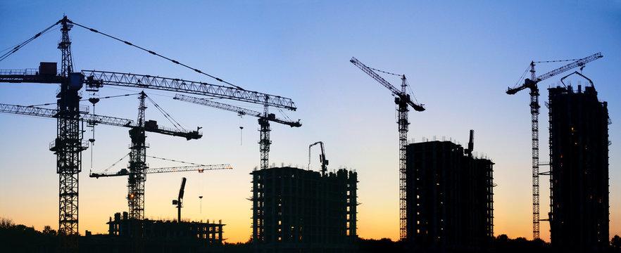 construction cranes silhouette sunset