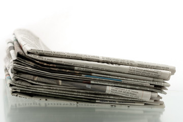 Heap of newspapers on shiny reflecting surface 2