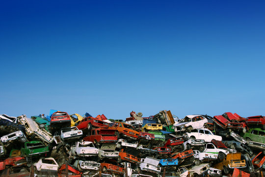 Pile of used cars in junkyard, ready for salvage