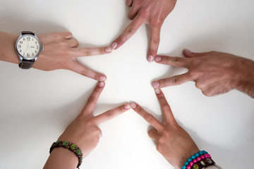 Five teenagers hands form a star.