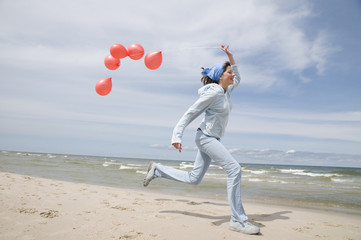 Teenager playing with balloons on the beach