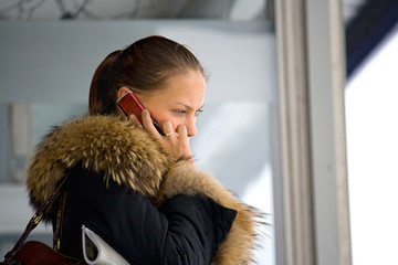 Speaking by phone young girl in winter