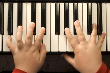 Childs hands playing a piano keyboard