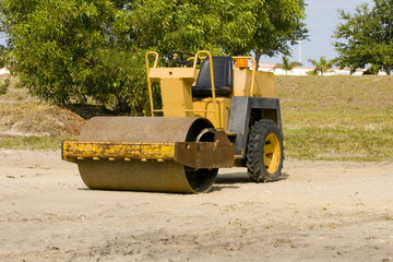 A small asphalt roller sits idle over the weekend