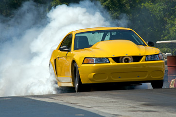 Smoke from the tires of a yellow racer