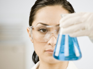 Female scientist looking at beaker of blue liquid