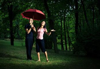 Young couple under umbrella.