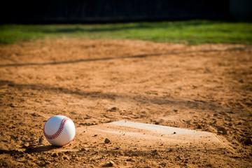 Baseball Sitting on a dirty homeplate.