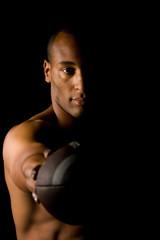 Man holding football, shirt off. moody, Athlete holding ball